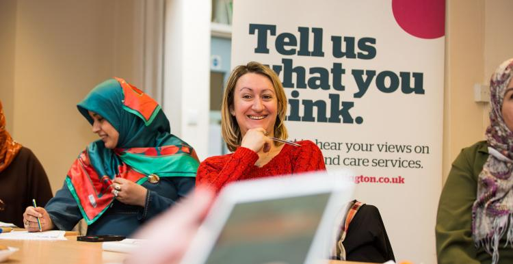Women smiling in front of poster that says 'tell us what you think'