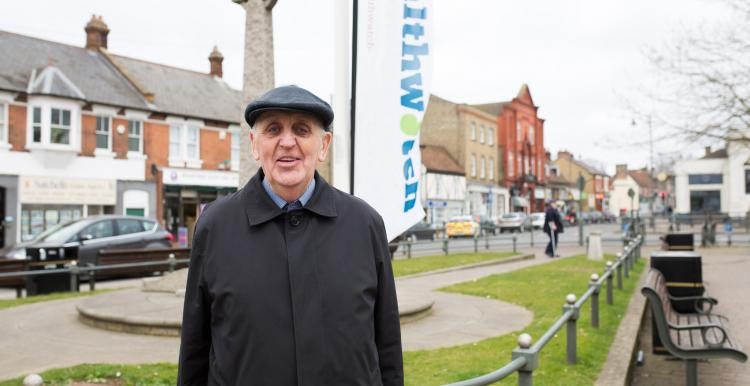 Elderly man wearing his hat and coat stood in front of a Healthwatch banner