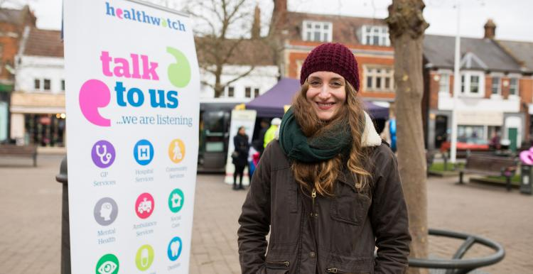 Young woman wearing a hat and scarf stood in front of a Healthwatch banner