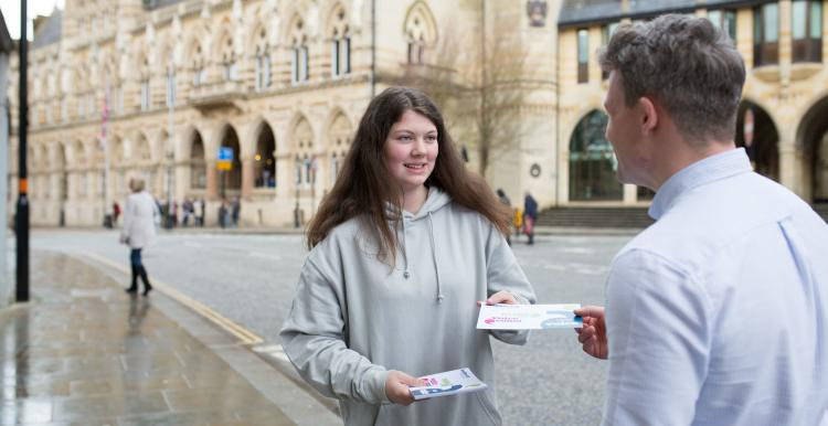 A teenage girl wearing a grey Healthwatch hoodie hands out a Healthwatch leaflet to a man