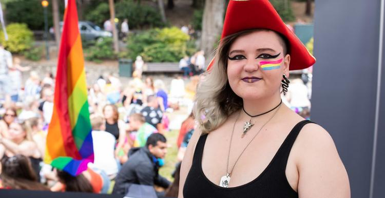 Woman at Pride with the Pansexual flag painted on her face
