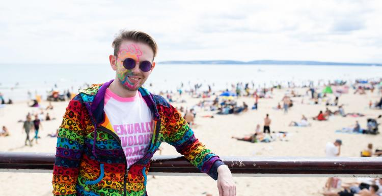 Man with colourful face paints standing in front of a beach