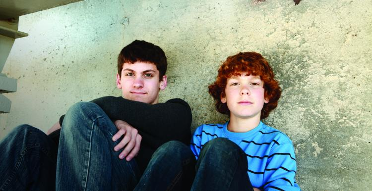 Two boys, sitting on the floor against a wall, smiling at the camera