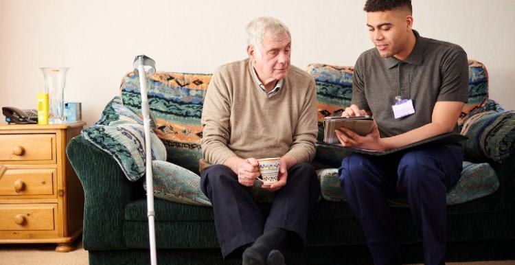 Carer sitting with elderly man on sofa