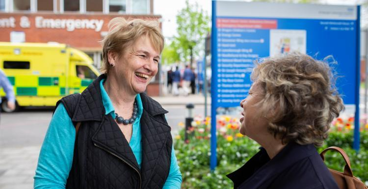 Two ladies talking outside a hospital