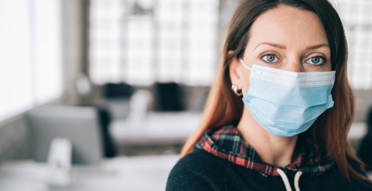 Woman wearing protective face mask in the office for safety and protection during COVID-19