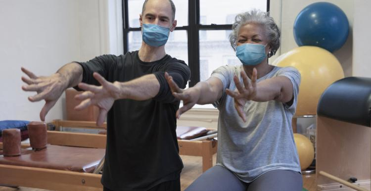 A man and women doing exercise at rehab center wearing masks