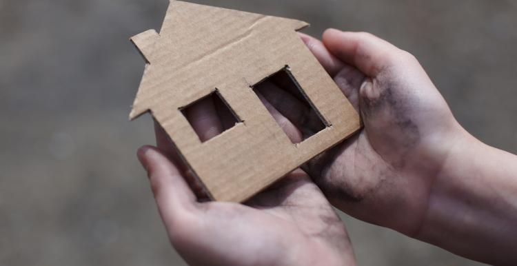 Person holding shape of a home in their hands
