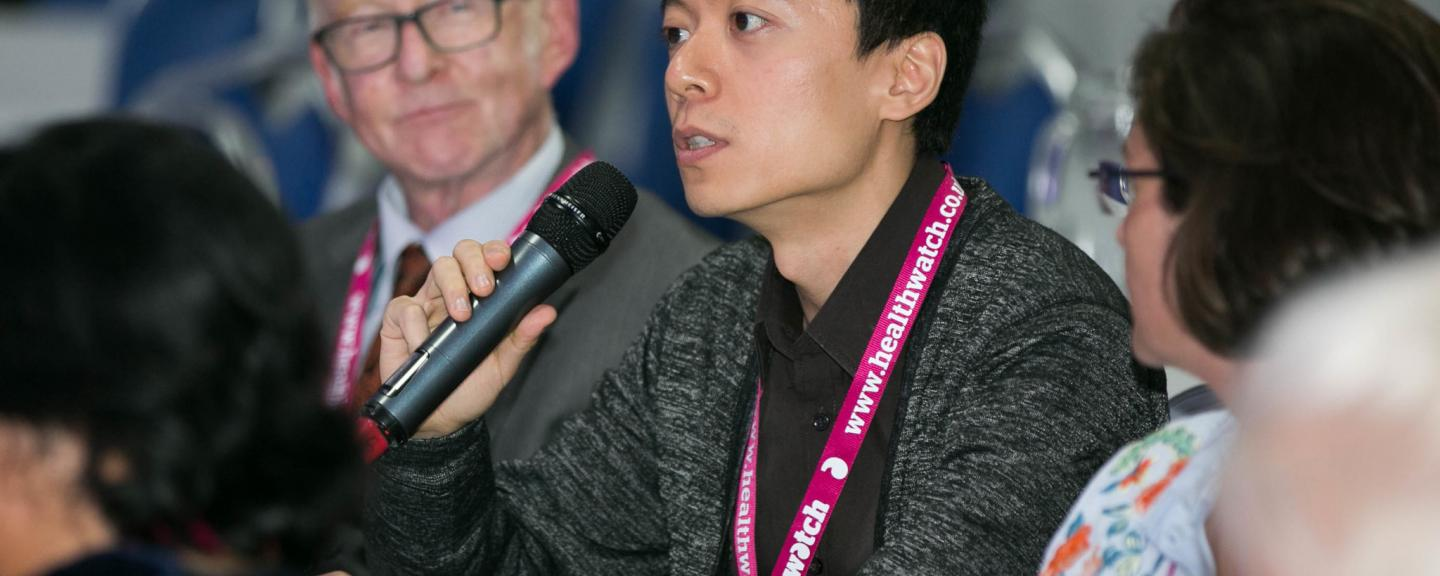 Man speaking into a microphone, asking a conference at a conference