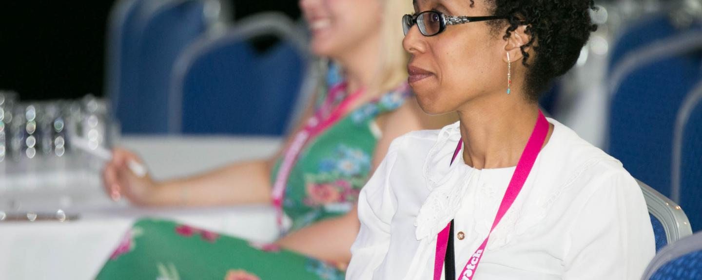 Woman sitting at a table at a conference