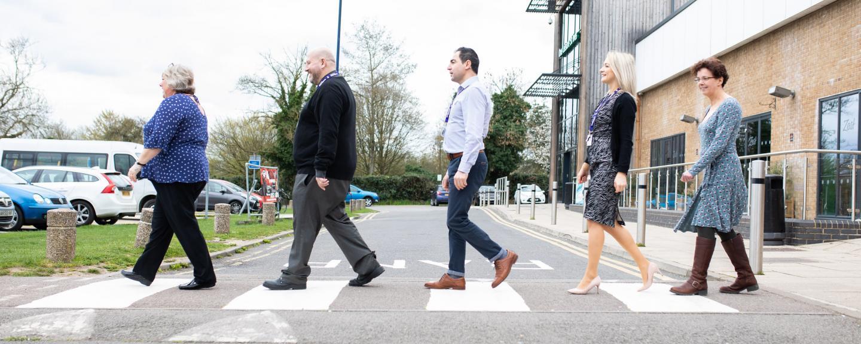 Group of Healthwatch employees walking across a cross roads