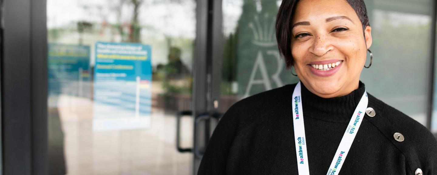 A woman smiling with a healthwatch lanyard on