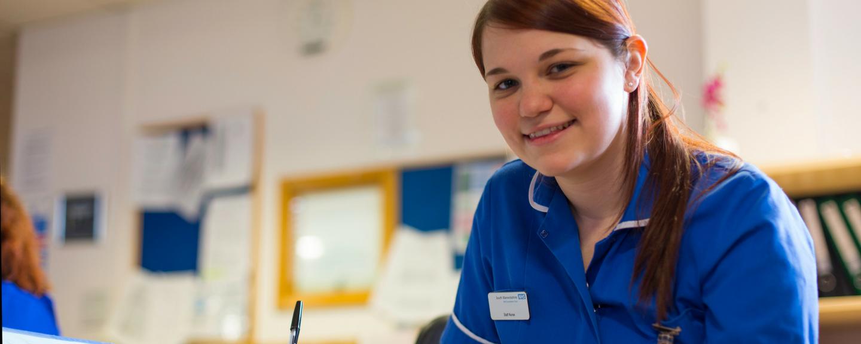 NHS staff member in uniform smiling