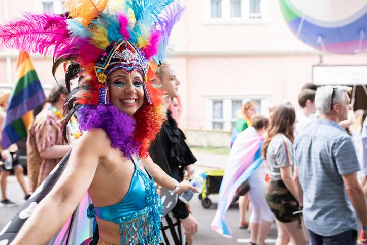 A woman in colourful clothing and feathers at Pride