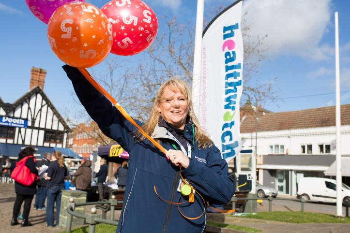 Female volunteer holding a bunch of balloons