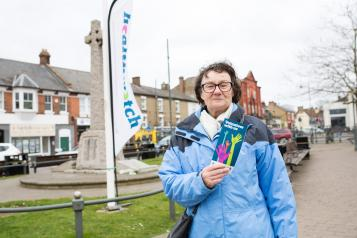 Woman stood outside in front of a Healthwatch flag