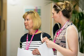 Woman with Healthwatch lanyards talking
