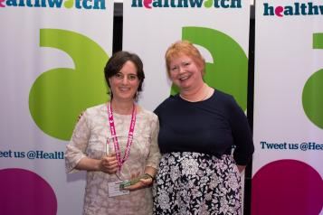 Two Healthwatch volunteers stood in front of a Healthwatch background