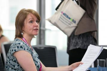 Healthwatch staff member sitting at a desk reading papers