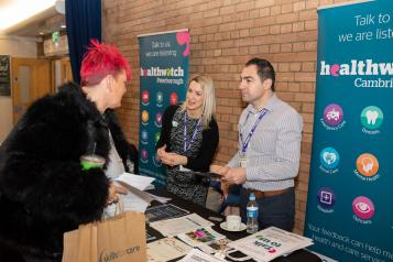 A woman with short red hair talking to a man and a woman behind a Healthwatch stall, at a community event.