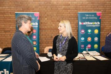 A staff member from Healthwatch Cambridgeshire speaking to someone at an event