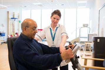 An older man in a blue jumper, being shown how to use a machine by a young female healthcare professional.