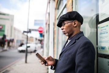 Man standing in the street looking at his phone