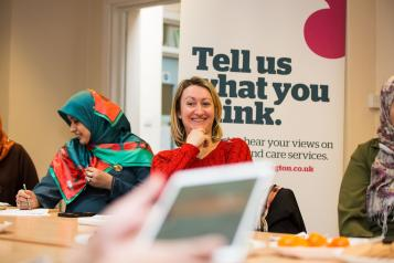 Women sitting in front of a Healthwatch poster and an iPad in the foreground