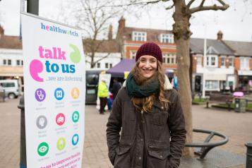 Woman standing next to a Healthwatch banner