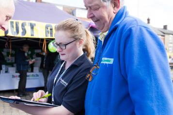 Healthwatch volunteers at an event looking at a clipboard
