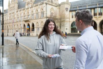 Young woman wearing a grey hoodie handing a leaflet to a man.