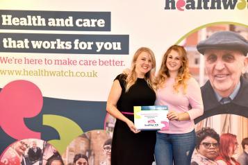 Two blonde women receiving a Healthwatch Network Award