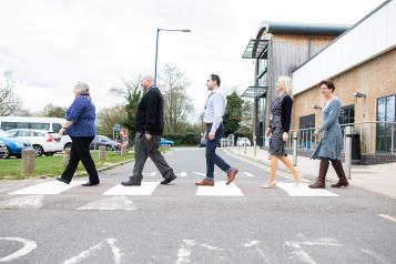 Group of Healthwatch employees walking across a cross roads