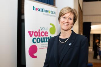 Woman in front of a sign that says 'Healthwatch - your voice counts'