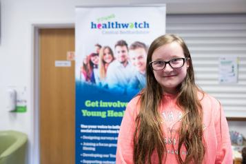 Teenage girl standing in front of a Healthwatch banner