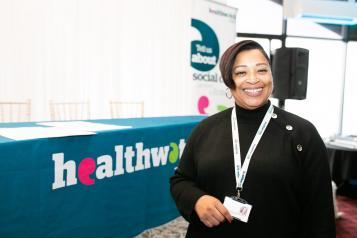 Female volunteer standing in front of a Healthwatch tablecloth