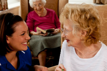 Care home staff talking to a resident