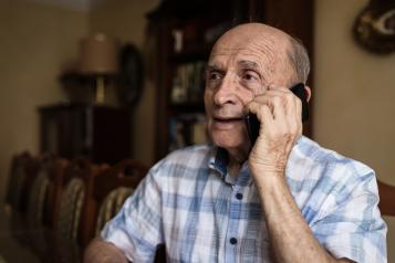 Elderly man resting at home and using mobile phone