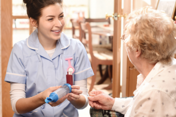 Nurse smiling at an old lady in a care home.