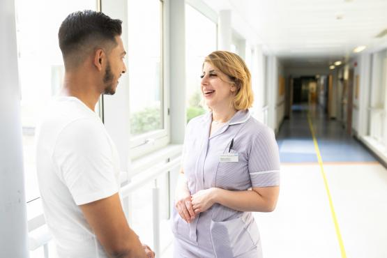 Man talking to a nurse in hospital corridor