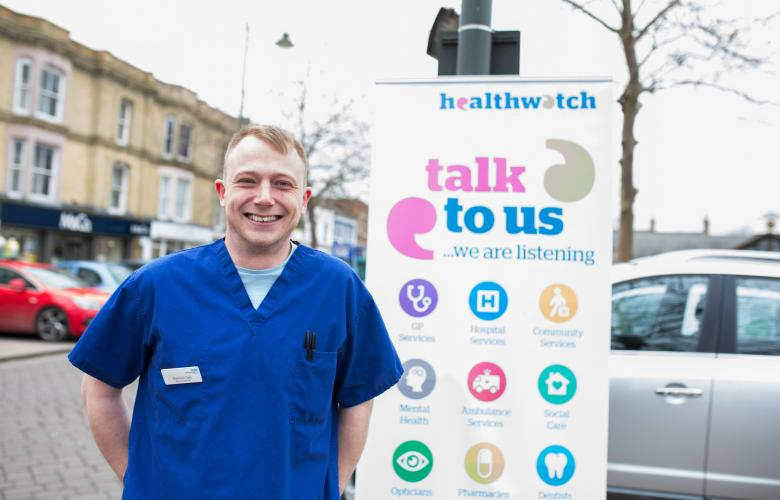 NHS professional standing in front of a Healthwatch sign that says 'talk to us'.
