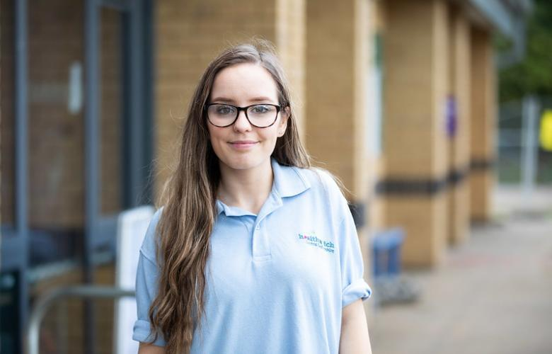 Young woman standing in a blue polo shirt