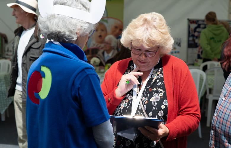 Healthwatch volunteer talking to a lady with a clipboard
