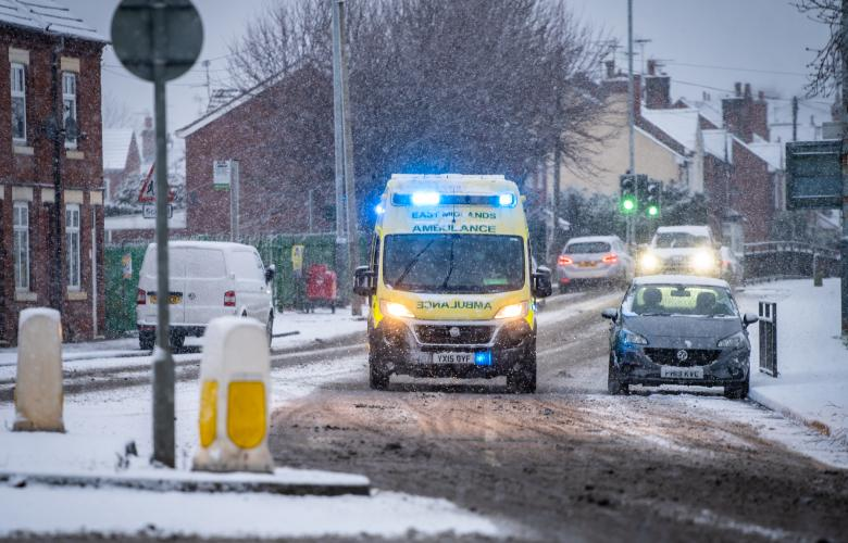 NHS EMAS Ambulance Service on 999 emergency response with snow on road blue lights during snowfall stock photo