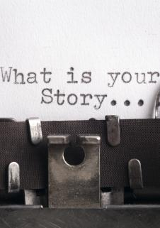 Type writer with 'What is your story' written on the page